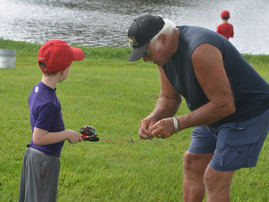 R.E. Thompson, right, helps Nathaniel Skinner, left, put  bait on a hook on Sunday afternoon at Pecan Lakes Subdivision in Sunrise.