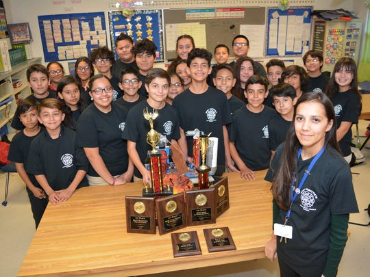 Chaparral Middle School math teacher Rina Viramontes poses with her MESA students and all the awards her robotic challenge students have won recently.