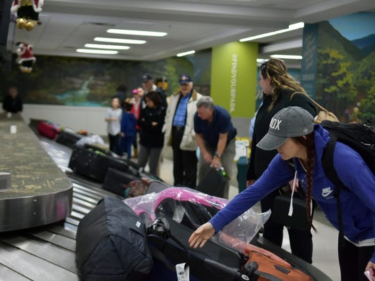 Passengers on Delta flight 2263 from Atlanta pick up baggage from the claim area at McGhee Tyson Airport.