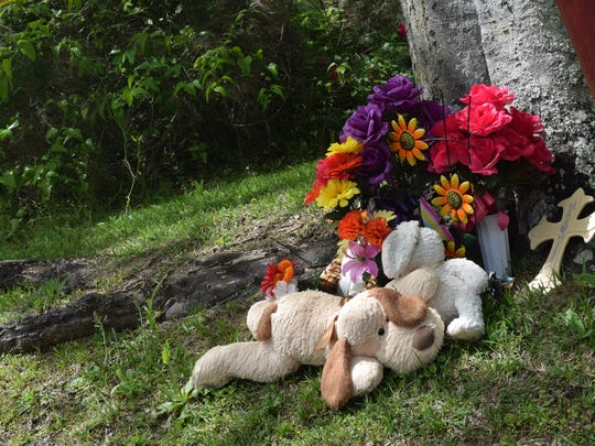 Flowers, plush animals and a cross sit under a tree
