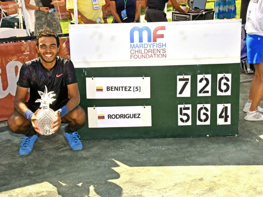 Juan Benitez poses by the final score of his final victory.