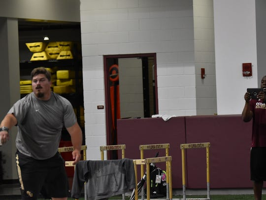 Austin Droogsma works out with FSU assistant coach Dorian Scott, who films one of his throws during a practice at FSU's indoor facility.