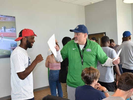 UWF football coach Pete Shinnick greets a player on July 13, prior inside the Argos new training center, prior to the football camp.