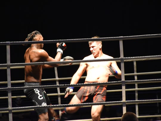 Former Washington High football player Sedarius (SD) Dumas, left, tangles with Cody Herbert in their bout Saturday night at Island Fights 49 at the Bay Center.