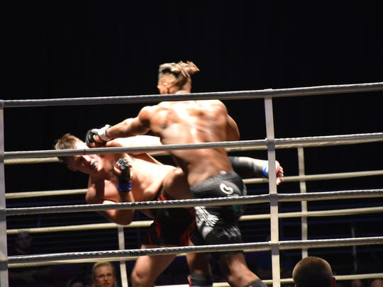 Former Washington High football player Sedarius (SD) Dumas lands a punch against Cody Herbert in their MMA bout Saturday night at Island Fights 49 at the Bay Center.
