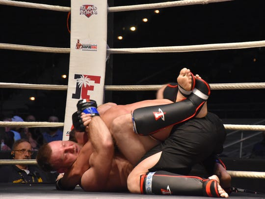 Jake Jensen gets a top hold on Greg Lee during their MMA amateur title bout Saturday night as co-main event in Island Fights  49.