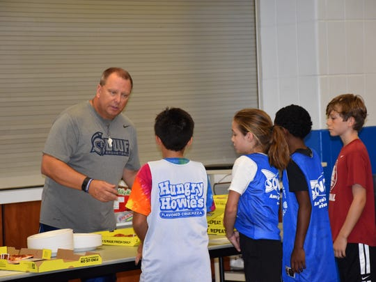 UWF men's basketball coach Jeff Burkhamer hands out pizza slices during a lunch break Wednesday at the fourth annual Shoot For the Stars youth basketball camp at the UWF Field House.