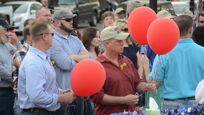Members of the Louisiana National Guard release balloons at a vigil Sunday in downtown Alexandria in memory of the 11 National Guardsmen who lost their lives in a nighttime training mission in Florida.