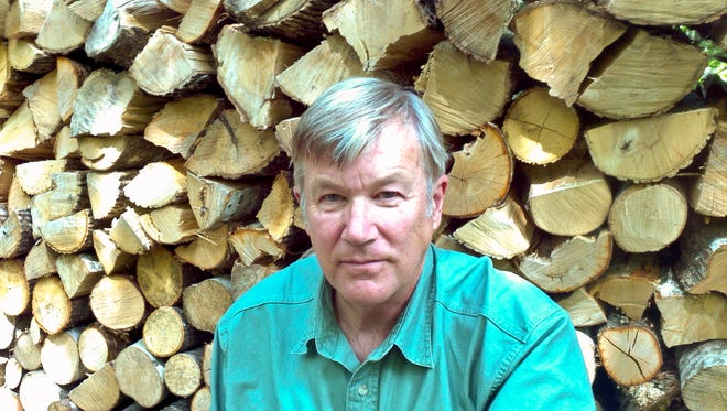 Mark Whitworth, executive director of Burke-based nonprofit Energize Vermont, pauses by a wood pile.