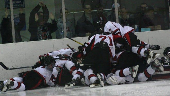 Livonia Churchill hockey players celebrate following Monday's 4-3 triple-overtime victory over Franklin.