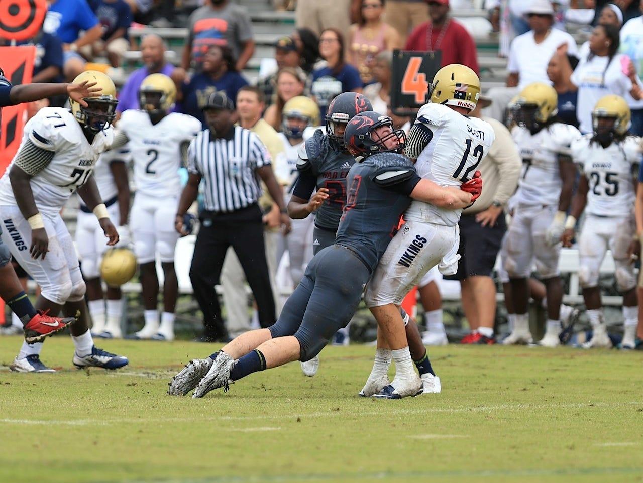 Spartanburg quarterback Austin Scott takes s smack from a Wakulla defender during Saturday's televised game on ESPN U.