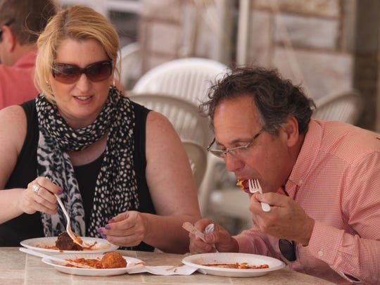 Donna Luzenski, left, and Larry de Garavilla dig in at a recent St. Anthony's Italian Festival in Wilmington.