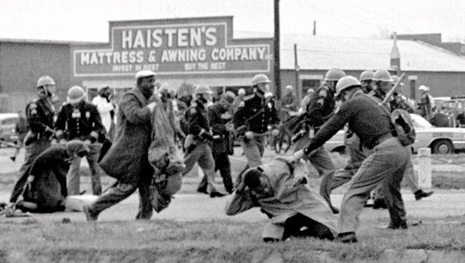 Alabama state troopers swing nightsticks to break up a civil rights voting march in Selma, Alabama, on March 7, 1965. John Lewis, front right, of the Student Non-violent Coordinating Committee, is put on the ground by a trooper. The Bloody Sunday march was followed weeks later by a march from Selma to Montgomery led by Martin Luther King Jr.