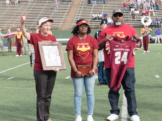 MSU President Dr. Suzanne Shipley presents Robert and Tammy Grays the retired jersey of their son, Robert Grays, who died following an on-field injury suffered Sept. 16, 2017. The Grays attended Saturday's final home game of the 2017 season.
