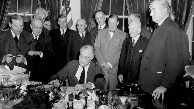 President Franklin D. Roosevelt signs the declaration of war on Dec. 8, 1941, after the Japanese bombing of Pearl Harbor the day before.