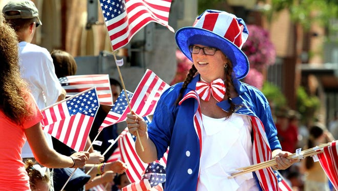 Kelley Schemansky passes out hundreds of American flags to spectators along the parade route during Brighton's annual Indfependence Day parade.