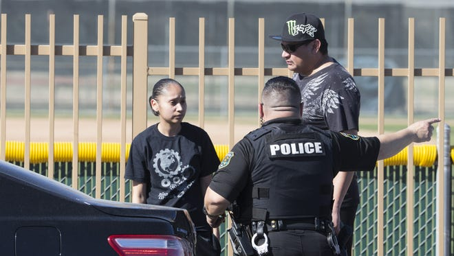 Glendale officer directs families where to go to reunite with their students from Independence High School in Glendale, Ariz., on Thursday, February 12, 2016, after a shooting occurred at the school.