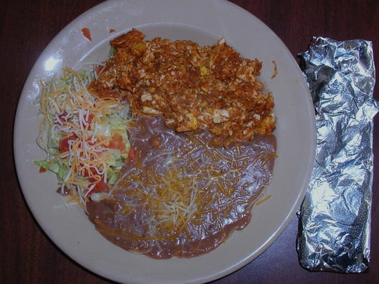 A traditional Mexican breakfast can be chorizo and eggs with beans and two tortillas.