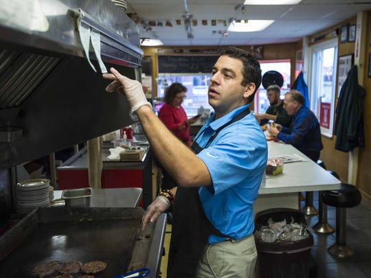 Earl Handy checks an order as he staffs the grill at Handy's Lunch in Burlington.
