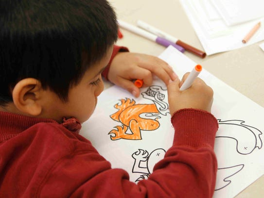 Joshua Ortiz, 6, colors a dragon shadow puppet during
