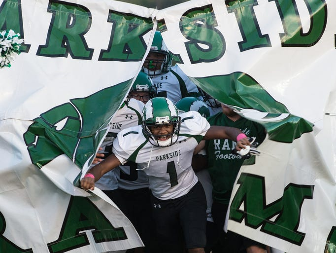 Parkside football players storm the field at the start
