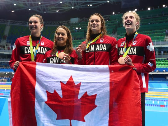 Aug 6, 2016: Canada members Sandrine Mainville , Chantal Van Landeghem , Taylor Ruck , Penny Oleksiak pose with their medals after the women's 4x100m freestyle relay finals during the Rio 2016 Summer Olympic Games at Olympic Aquatics Stadium.