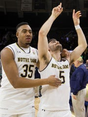 Notre Dame's Bonzie Colson (35) and Matt Farrell (5) walk off the court together during following their senior night in an NCAA college basketball game.