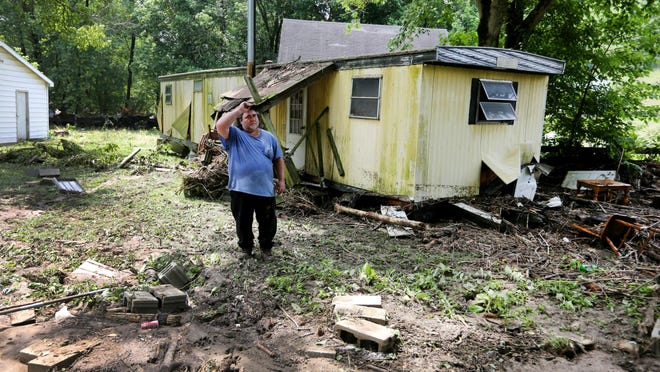 Downing, walks around his property in Ripley. His mobile home had previously been in the foreground where the bricks are prior to a late evening flash flood. His half-sister, Victoria Kennerd, lived next door, closer to the Red Oak Creek. Their mobile home was swept completely off its foundation. Kennerd and her two youngest children were killed. Her fiancé, Marco Barrios, and two older boys survived.