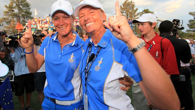 Suzann Pettersen of Norway and Liselotte Neumann of Sweden and The European Team celebrate after Europe beat America 18-10 in the 2013 Solheim Cup in Parker, Colorado.