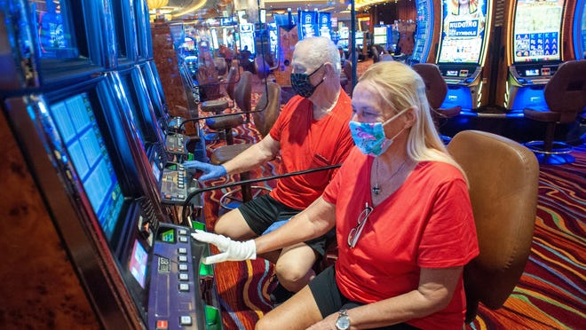 Bob and Sally Hagy of Burlington, New Jersey, are separated by a partition as they play slot machines at Parx Casino on Monday.