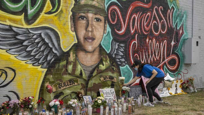 Mellisa Mendoza places white roses at a mural for Fort Hood Spc. Vanessa Guillen at a convenience store in the Dove Springs neighborhood on July 6. A public memorial will be held Friday for Guillen, who was killed by another soldier earlier this year.