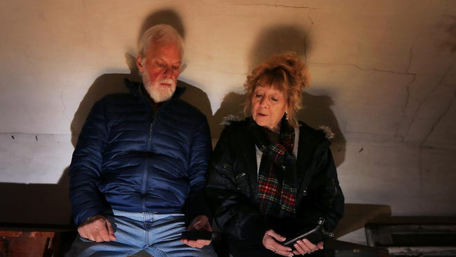 Willy Hassell and Lynne Nickerson watch a K-II electromagnetic field meter as they talk to what they believe is the spirit of Frank James at the historic James House in Hampton.