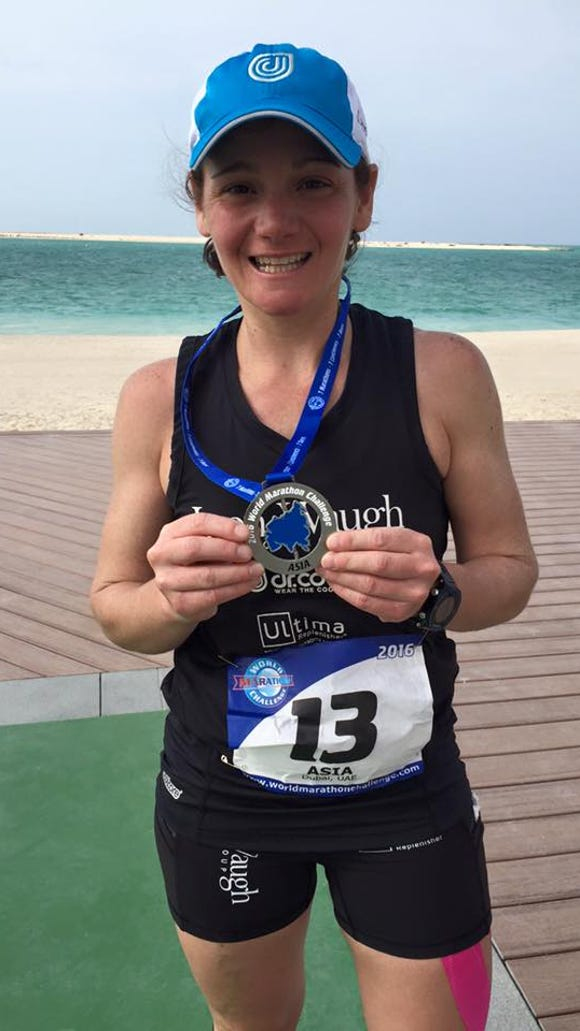 Becca Pizzi shows off her gold medal after winning the Dubai Marathon, her sixth in a row in the World Marathon Challenge.