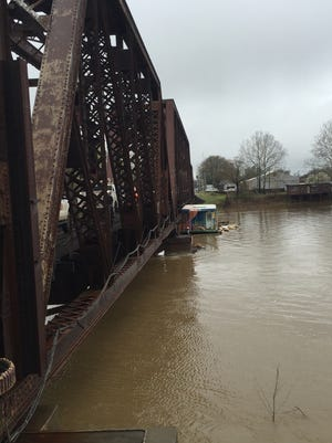 A houseboat was pinned against the Ouachita River railroad bridge in Monroe Saturday morning.