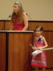 Coral Brennan, 7, listens to her mother, Tess Brennan, speak out against common Core testing Wednesday (8/27/14) during a school board meeting at the Lee County Education Center in Fort Myers. Lee County is the first in Florida to opt out of Common Core.