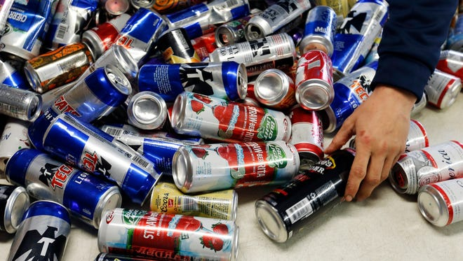 Ben Allen sorts through a table full of cans Thursday, March 16, 2017, the Kans R Us redemption center in Perry, Iowa.
