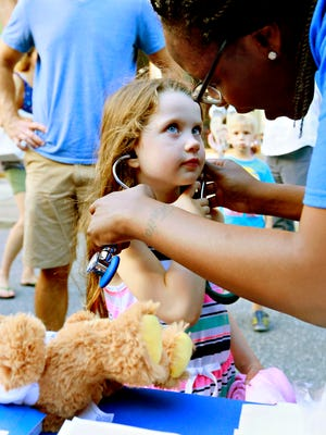 Medical assistant Brittany Copeland, of WellSpan Pediatric Medicine on East Market Street, helps Laurel Harrison, 5, of Spring Garden Township, listen through a stethoscope for a teddy bear checkup during First Friday festivities in York City, Friday, Aug. 4, 2017. WellSpan is the presenting sponsor of Downtown Inc's First Fridays and was promoting and providing information regarding Pennsylvania's immunization requirements. Dawn J. Sagert photo