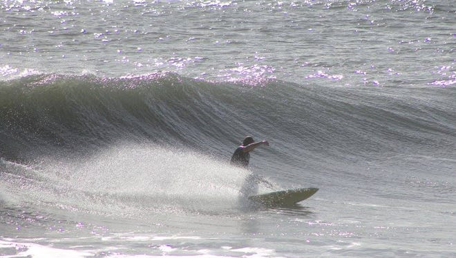 Bill May, of Satellite Beach, cranks a big bottom turn on a backside wave. Warmer weather and better waves will have Brevard surfers smiling all weekend.