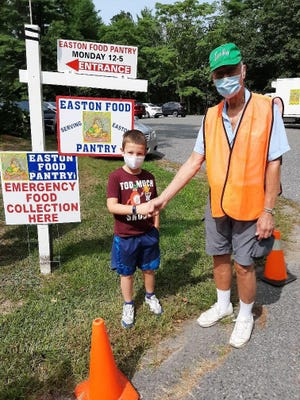 Cole Aronstein of Easton, left, shown with Food Pantry Director Ken Wood, raised $500 in cash and groceries for the pantry in August with a lemonade stand.