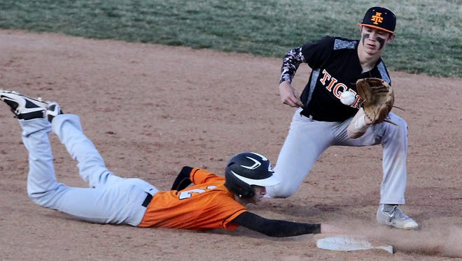 Aztec's Jake Taylor tries to tag out Montezuma-Cortez' Cutter Mathews at second base during Friday's game in Aztec.