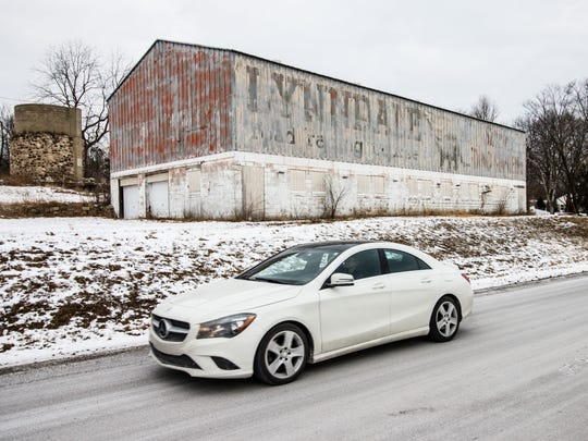 The paint on the side of an old white barn has chipped away, revealing a decades-old sign advertising for the now-defunct Lynndale Race Track. The track operated for several years in the 1960s.