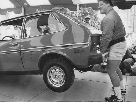 Tom Zupancic lifts a Ford Fiesta during a demonstration at Central Library in 1987.