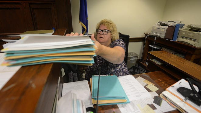 Deputy Clerk of Courts June Heisler goes through a stack of payment review files. The folders contain criminal cases where the defendant was ordered to pay but has not complied.