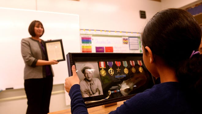 Montana Superintendent of Public Instruction Denise Juneau shares military medals earned by her grandfather for his Army service with sixth-graders at Loy Elementary School on Thursday.