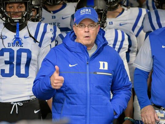 Duke coach David Cutcliffe leads his team onto the
