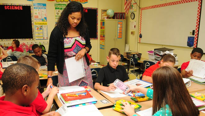 Fourth grade inclusion teacher Shallon Swanier talks with students as they go over schedules and classroom procedures on the first day of school at Petal Elementary.