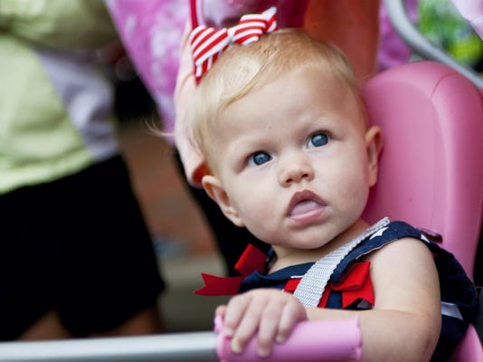 Eleven month old Aribella Kreps-Null watches the Independence Day parade with her parents Saturday during the Independence Day parade along Main Street in Waynesboro.