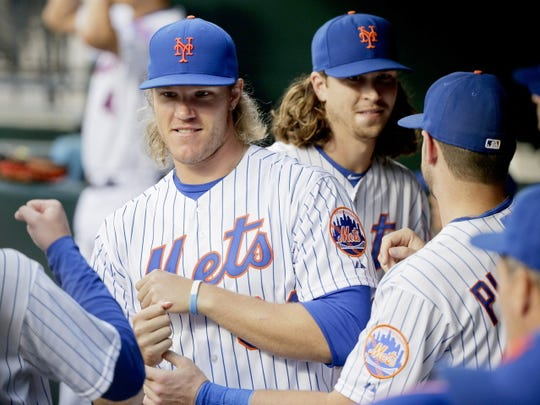 New York Mets' Noah Syndergaard, left, and Jacob deGrom pump fists with teammates before a baseball game against the Colorado Rockies, Monday, Aug. 10, 2015, in New York. (AP Photo/Julie Jacobson)