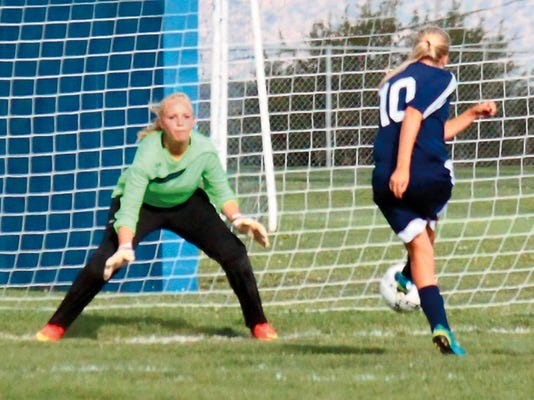 Danny Udero - Sun-News Photo   Taylor Rinehart (10)  meets the Silver High goal keeper head-on in a point-blank shot. Rinehart's goal in the first half kept pace with the host Fighting Lady Colts on Thursday in Silver City.