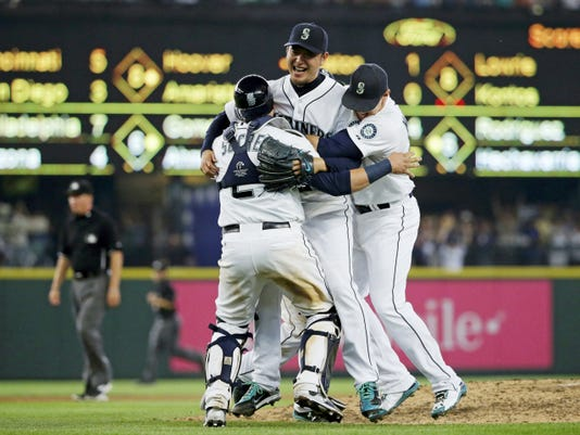 Seattle starting pitcher Hisashi Iwakuma, top, is mobbed by teammates including catcher Jesus Sucre (2) after Iwakuma threw a no-hitter against the Baltimore Orioles on Wednesday in Seattle. The Mariners beat the Orioles, 3-0.